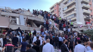 Rescue workers and local people try to reach residents trapped in the debris of a collapsed building, in Izmir, Turkey, on Oct. 30, 2020. (Ismail Gokmen / AP)