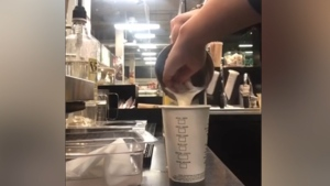 Screenshot from a video posted to TikTok shows a barista making a drink with their hands.