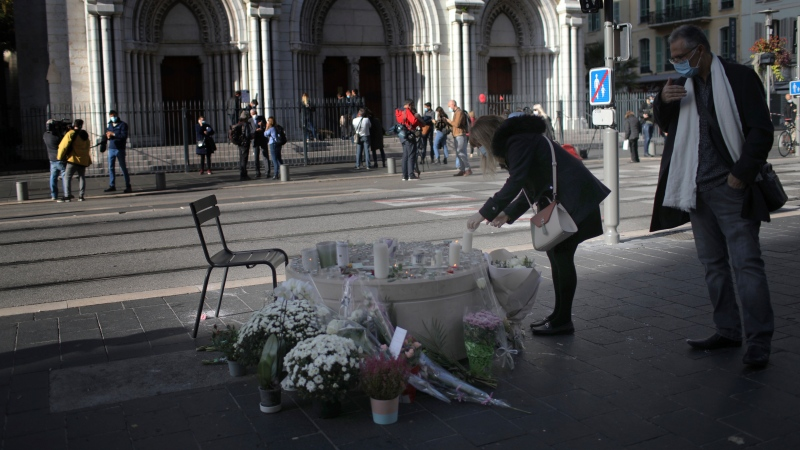 A woman lights a candles in front of the Notre Dame church, in Nice, France, Friday, Oct. 30, 2020. A new suspect is in custody in the investigation into a gruesome attack by a Tunisian man who killed three people in a French church. France heightened its security alert amid religious and geopolitical tensions around cartoons mocking the Muslim prophet. (AP Photo/Daniel Cole)