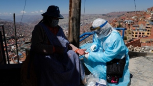 A healthcare worker dressed in full protective gear draws blood from a woman to test for the new coronavirus during a house-to-house COVID-19 testing campaign, in the Villa Rosasani neighbourhood of La Paz, Bolivia, on Aug. 28, 2020. (Juan Karita / AP)