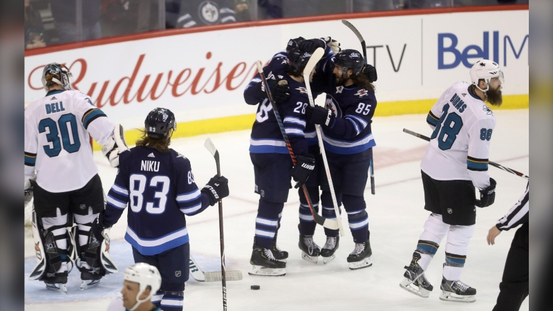 Winnipeg Jets' Sami Niku (83), Jack Roslovic (28), Andrew Copp (9) and Mathieu Perreault (85) celebrate after Copp scored on San Jose Sharks goaltender Aaron Dell (30) with Brent Burns (88) in front during first period NHL hockey action in Winnipeg, Tuesday, March 12, 2019. THE CANADIAN PRESS/Trevor Hagan