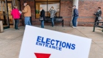 Voters line up as the doors open to the Election Center for absentee early voting for the general election in Sterling Heights, Mich., Thursday, Oct. 29, 2020. (AP Photo/David Goldman)