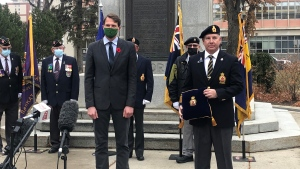 Mayor Charlie Clark receives the first poppy from Brent Wignes, chairman of Saskatoon Remembrance Day Citizen Committee. (Kaitlyn Schropp/CTV Saskatoon)