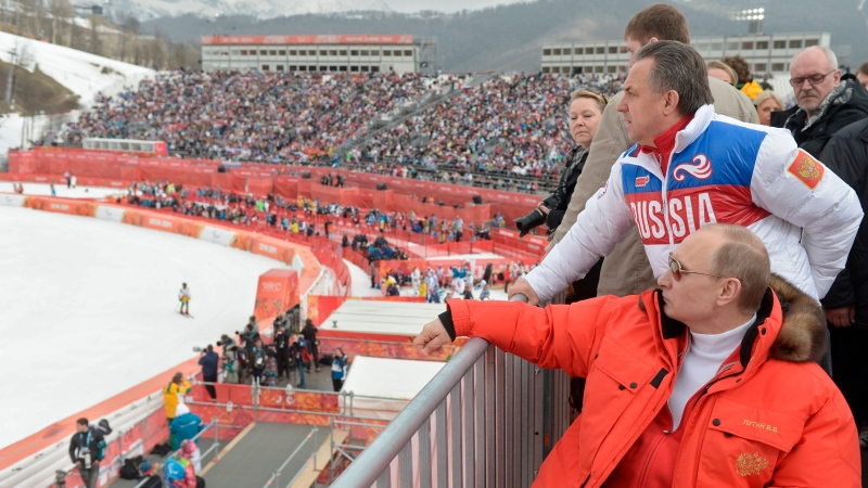 In this file photo taken Saturday, March 8, 2014, Russian President Vladimir Putin, foreground, and Russia's sports minister Vitaly Mutko, standing behind, watch downhill ski competition of the 2014 Winter Paralympics in Roza Khutor mountain district of Sochi, Russia. Russia's status as an Olympic team and reputation as a serial cheater in international sports goes on trial on Monday Nov. 2, 2020, as the Court of Arbitration for Sport will start hearings about a manipulated database from the Moscow testing laboratory. (Alexei Nikolsky, Sputnik, Kremlin Pool Photo via AP, File)