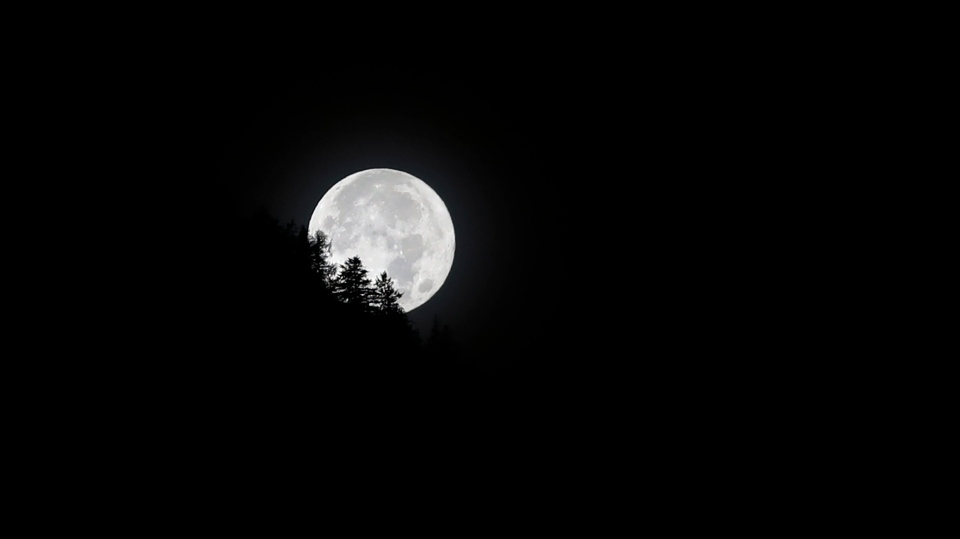 The full moon sets on early Friday morning in Bad Reichenhall, Germany, Friday, Oct. 2, 2020. (AP Photo/Matthias Schrader)
