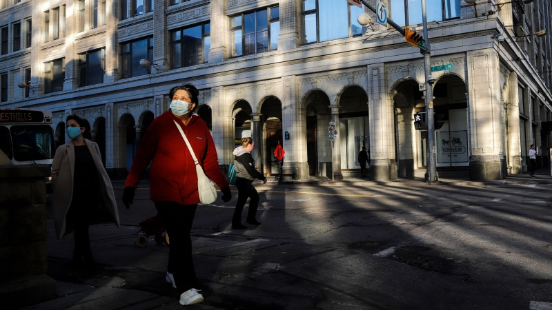 A woman wears a mask in downtown Calgary, Alta., Friday, Oct. 30, 2020, amid a worldwide COVID-19 pandemic. THE CANADIAN PRESS/Jeff McIntosh