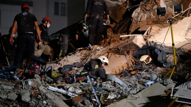 Members of rescue services search in the debris of a collapsed building for survivors in Izmir, Turkey, early Saturday, Oct. 31, 2020. A strong earthquake struck Friday in the Aegean Sea between the Turkish coast and the Greek island of Samos, killing several people and injuring hundreds amid collapsed buildings and flooding. (AP / Emrah Gurel)