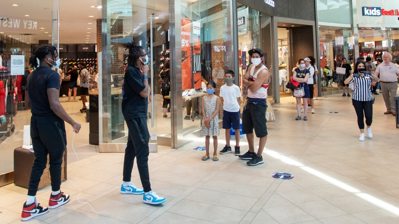 Shoppers line up at a store in Carrefour Laval shopping center as malls across Quebec reopened amid the COVID-19 pandemic, Friday, June 19, 2020 in Laval, Que.THE CANADIAN PRESS/Ryan Remiorz