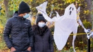 A couple wearing protective masks walk past a house decorated for Halloween during the COVID-19 pandemic in Montreal, on Friday, October 30, 2020. THE CANADIAN PRESS/Paul Chiasson
