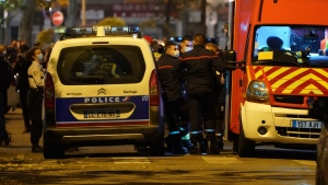Police officers and rescue workers block the access to the scene after a Greek Orthodox priest was shot Saturday Oct.31, 2020 while he was closing his church in the city of Lyon, central France. (AP Photo/Laurent Cipriani)
