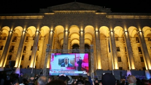 Supporters of Georgian ex-President Mikheil Saakashvili's United National Movement watch his address on a big screen in front of the Parliament's building after the parliamentary elections in Tbilisi, Georgia, Saturday, Oct. 31, 2020. (AP Photo/Zurab Tsertsvadze)