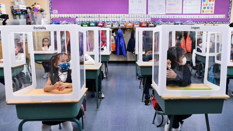 Children wearing masks sit behind screened in cubicles as they learn in their classroom after getting their pictures taken at picture day at St. Barnabas Catholic School during the COVID-19 pandemic in Scarborough, Ont., on Tuesday, October 27, 2020.