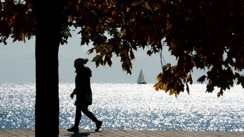 A woman walks along the boardwalk by Lake Ontario in Toronto on Saturday October 31, 2020. THE CANADIAN PRESS/Frank Gunn