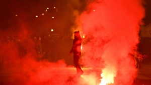A left-wing activist walks past flares as they take part in a protest rally to demand economic support measures, as the government announced a new series of restrictions to contain the spread of COVID-19 and considers more stringent measures, in Rome. (AFP)