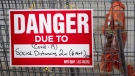 A construction sign on a fence surrounding an excavation indicates the danger is Covid-19 as a construction worker walks past Tuesday October 27, 2020 in Ottawa. THE CANADIAN PRESS/Adrian Wyld