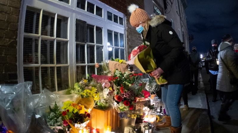 Neighbor Marie-France Rioux brings flowers at a vigil to honour Suzanne Clermont who was stabbed to death on Halloween night by a man with a sword, Monday, November 2, 2020 in Quebec City. Rioux tried to save Clermont's life the night of the stabbing. THE CANADIAN PRESS/Jacques Boissinot