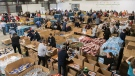 Volunteers place donated food items into boxes at the Moisson Montreal food bank in Montreal, Saturday, December 7, 2019. THE CANADIAN PRESS/Graham Hughes