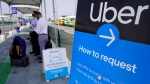 In this Aug. 20, 2020, file photo travelers request an Uber ride at Los Angeles International Airport's LAX-it pick up terminal. (AP Photo/Damian Dovarganes, File)
