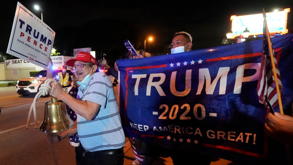 In this Nov. 3, 2020, photo, Rafael Fagundo rings a bell as he and other supporters of U.S. President Donald Trump chant and wave flags outside the Versailles Cuban restaurant during a celebration on election night in the Little Havana neighborhood of Miami. (AP Photo/Wilfredo Lee)