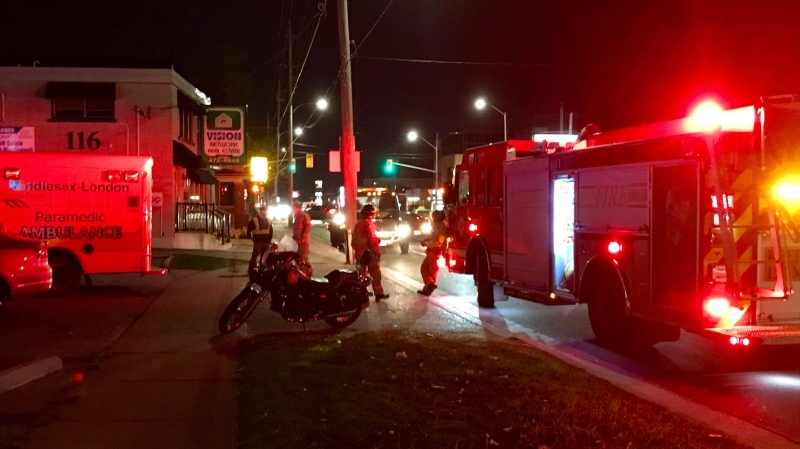 London firefighters walk back to their engine after standing up a motorcycle involved in a crash on Thursday, Nov. 5, 2020. (Sean Irvine / CTV News)