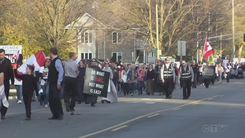 Protesters march in an anti-COVID-19 restrictions rally in Aylmer, Ont. on Nov. 7, 2020.