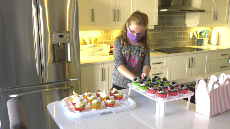 Sophie George, 8, making cupcakes. She's selling them to raise money for the Ottawa Hospital Foundation's COVID-19 Emergency Response Fund. (Shaun Vardon / CTV News Ottawa)