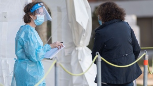 A health-care worker talks to a woman at a COVID-19 testing clinic in Montreal, Sunday, November 8, 2020, as the COVID-19 pandemic continues in Canada and around the world. THE CANADIAN PRESS/Graham Hughes