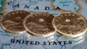 Canadian dollar coins are displayed on a map along the border of Canada and the United States of America, in Montreal in a January 9, 2014, file photo. THE CANADIAN PRESS/Paul Chiasson