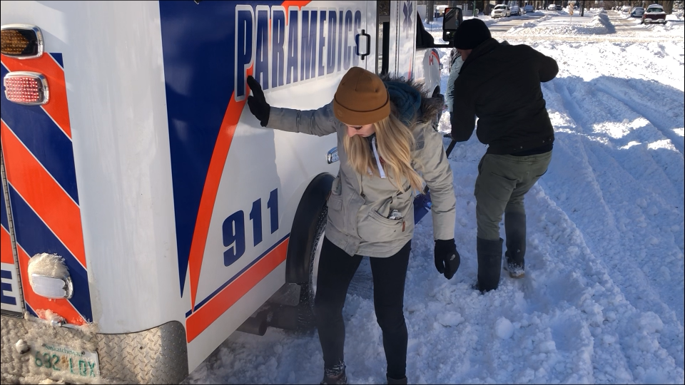 Bystanders pitch in to help free an ambulance stuck on an uncleared street in Saskatoon. (Chad Hills/CTV News)