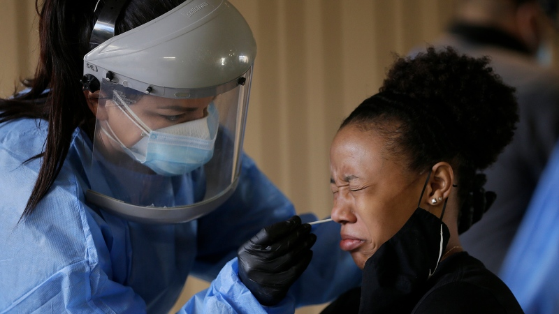 A student at The University of Texas is tested for coronavirus Friday, Oct. 16, 2020, at the UTEP Fox Fine Arts Center in El Paso, Texas. (Mark Lambie/The El Paso Times via AP)