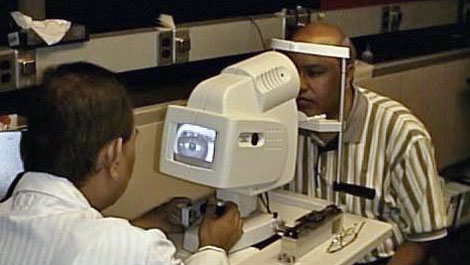 Dr. Manuel Datiles of the National Eye Institute, left, tests an eye device on NASA scientist Rafat Ansari. (AP/NASA)