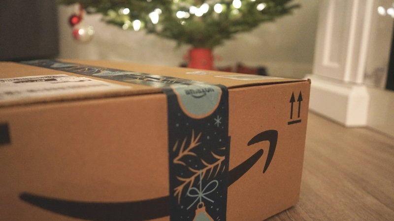 Amazon delivery box with gifts in front of a Christmas tree. (Photo by Wicked Monday on Unsplash)