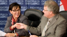 Minister of Health Leona Aglukkaq laughs as she shakes hands with Chief Public Health Officer David Butler-Jones following a news conference in Ottawa, Wednesday, Oct. 21, 2009. (Adrian Wyld / THE CANADIAN PRESS)