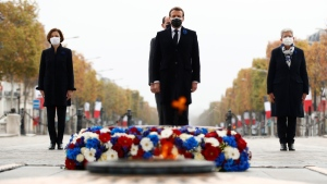 French President Emmanuel Macron, centre foreground, French Prime Minister Jean Castex, centre background, and French Defence Minister Florence Parly, left, stand at the tomb of the unknown soldier under the Arc de Triomphe during Armistice Day ceremonies marking the end of the First World War, in Paris, on Nov. 11, 2020. (Yoan Valat / Pool via AP)