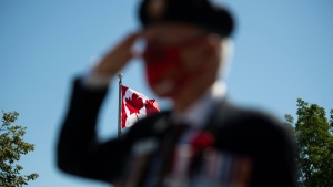 The Canadian flag is seen as a veteran salutes during a ceremony marking the 75th anniversary of V-J Day and the end of the Second World War, in Ottawa, on Saturday, Aug. 15, 2020. (THE CANADIAN PRESS / Justin Tang)