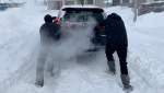 Saskatoon residents push a car through the snow on Nov. 11, 2020. (Laura Woodward/CTV Saskatoon)
