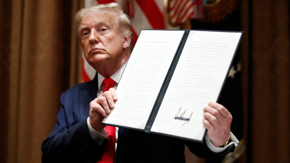 Trump holds up a signed Executive Order