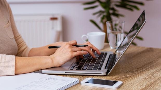 A woman can be seen working in front of a computer. (Branislav Nenin/Shutterstock)