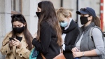 People wear face masks as they wait to enter a coffee shop in Montreal, Sunday, November 8, 2020, as the COVID-19 pandemic continues in Canada and around the world. THE CANADIAN PRESS/Graham Hughes