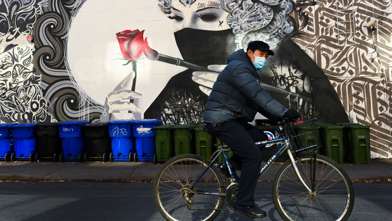 A man wearing a protective mask rides his bicycle past a face mask mural during the COVID-19 pandemic in Toronto on Thursday, November 12, 2020. THE CANADIAN PRESS/Nathan Denette