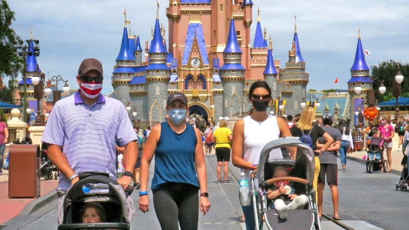 Guests walk on Main Street, U.S.A., in front of Cinderella Castle in the Magic Kingdom at Walt Disney World, in Lake Buena Vista, Fla., on Sept. 30, 2020. (Joe Burbank / Orlando Sentinel via AP)