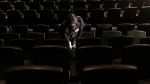 Cineplex employee cleaning seats at a movie theatre in Toronto, on Oct. 6, 2020. (Chris Young / THE CANADIAN PRESS)