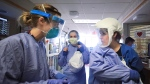 Medical staff attending to patients stricken with COVID-19 don protective equipment in a unit dedicated to treatment of the novel coronavirus at UW Health in Madison, Wis. Thursday, Nov. 5, 2020. Until recently, the hospital had four wings for coronavirus patients. To meet growing demand, it added another wing. (John Hart/Wisconsin State Journal via AP)