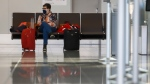 A passenger awaits her flight at the Calgary Airport in Calgary, Alta., Friday, Oct. 30, 2020, amid a worldwide COVID-19 pandemic. THE CANADIAN PRESS/Jeff McIntosh