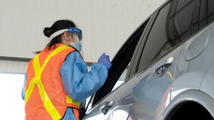 Ottawa Health personnel speaks with the driver before administering a COVID-19 test at a drive-through test centre in Ottawa, Friday, September 4, 2020. THE CANADIAN PRESS/Adrian Wyld