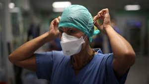 A nurse adjusts her mask in a COVID-19 area in a Marseille hospital, southern France, Thursday, Sept.10, 2020. As the Marseille region has become France's latest virus hotspot, hospitals are re-activating emergency measures in place when the pandemic first hit to ensure they're able to handle growing new cases. (AP Photo/Daniel Cole)