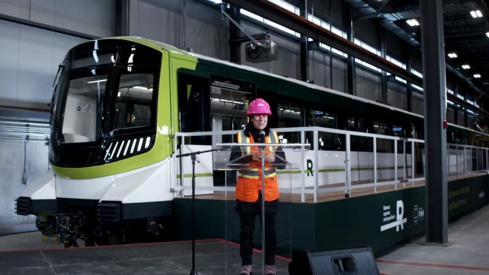 Montreal Mayor Valerie Plante stands in fromt of one of the new REM train cars.