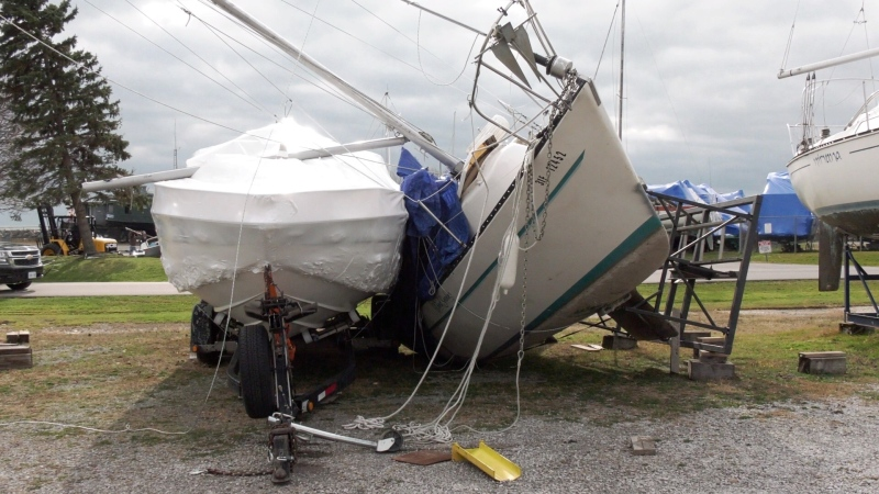 A sailboat leans against another one after it was blown over in Sunday's storm in Port Dover. (Marek Sutherland / CTV London)