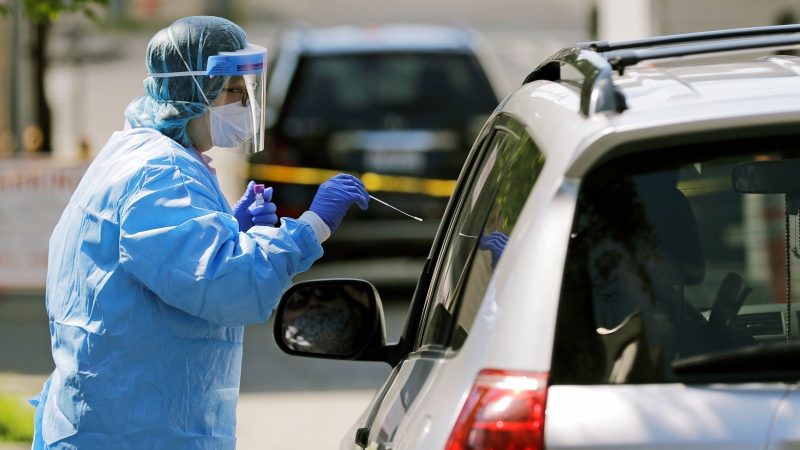 A nurse takes a swab sample from a patient during drive-up testing for COVID-19 on May 15, 2020. (AP Photo)