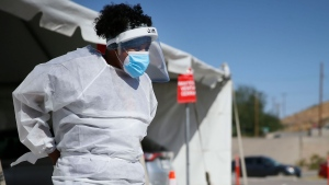 In this Oct. 26,2020, file photo, a medical worker stands at a COVID-19 state drive-thru testing site at UTEP, in El Paso, Texas. (Briana Sanchez/The El Paso Times via AP, File)